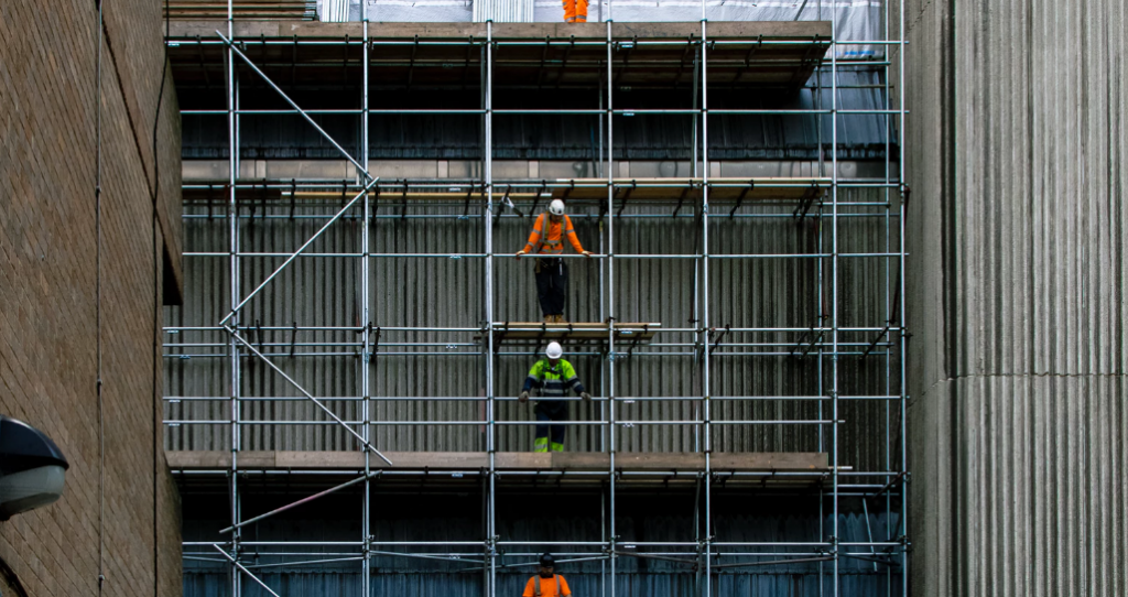 Men waiting among scaffolding and construction